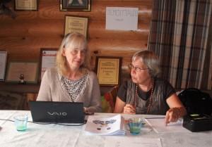 Sukuseuran sihteeri Sirpa Paltemaa kokouksen konttoristina statistinsa Annikki Hämäläisen kanssa kokousväen vastaanotossa v. 2010.